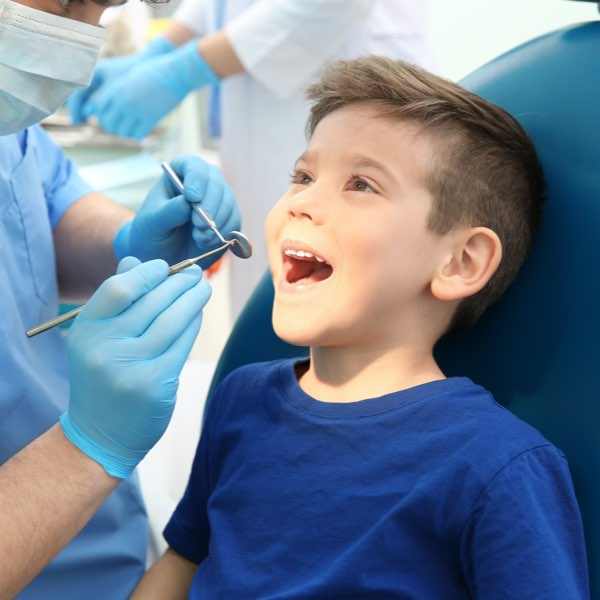 Male child getting teeth examined